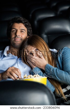 Scared mid adult woman leaning on man while watching movie in cinema theater - stock photo