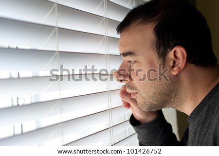 Scared or annoyed man peeks out the window through the blinds. - stock photo