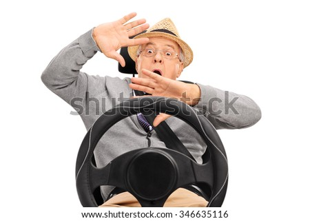Scared senior man sitting on a car seat fastened with seatbelt and gesturing with his hands isolated on white background - stock photo