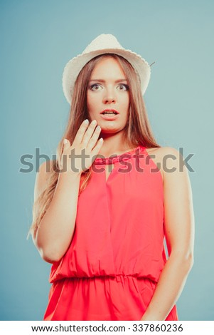 Scared shocked young woman girl in red shirt and straw hat in studio on blue. Summer female fashion vogue. - stock photo