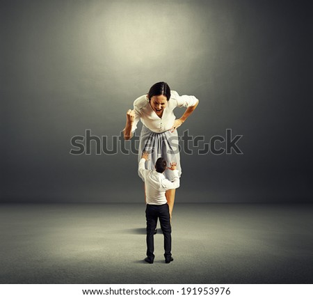 scared small man and screaming angry woman over dark background - stock photo