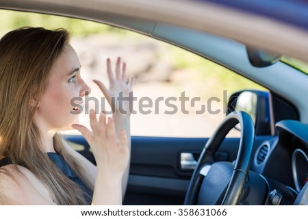 Scared woman behind the wheel brakes. The woman behind the wheel concept. Dangerous driving concept - stock photo