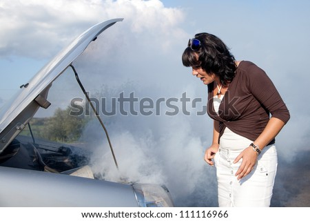 Scared woman nearby the smoking car - stock photo