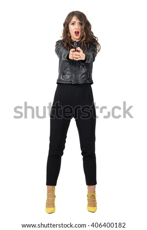 Scared woman shooting a gun at camera. Full body length portrait isolated over white studio background. - stock photo