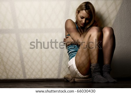Scared woman sitting on floor with windows grid shadows. - stock photo