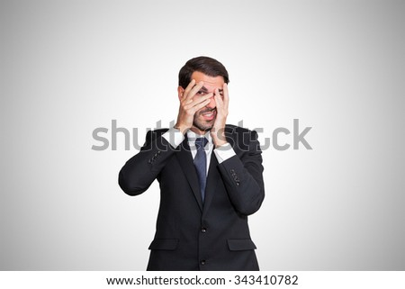 Scared young business man partially hiding his eyes. - stock photo