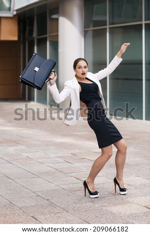 Scared young businesswoman protecting with briefcase and gesturing fear on city background - stock photo