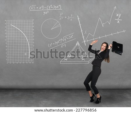 Scared young businesswoman with briefcase and gesturing fear in dark room with graphs - stock photo