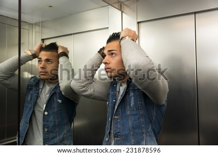 Scared young man desperate in stuck elevator with hands on his head - stock photo