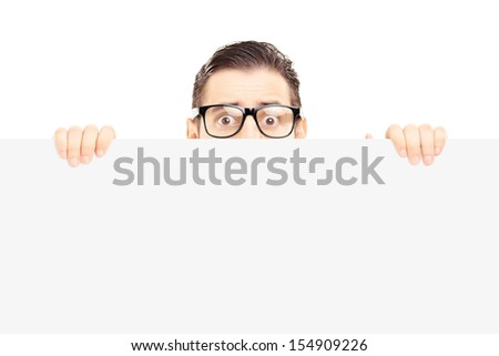 Scared young man with glasses hiding behind a blank panel isolated on white background - stock photo