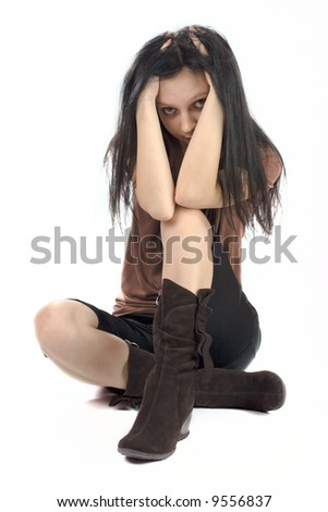 Scared young woman sitting on the floor isolaed on white - stock photo