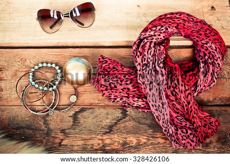 Scarf, bracelets, sunglasses and perfume on a wooden background - stock photo
