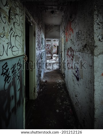 Scary abandoned corridor with hidden hand - stock photo