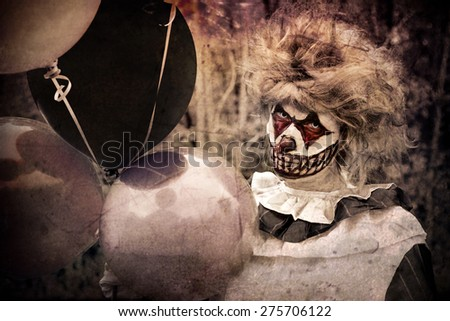 Scary clown holding dark balloons - stock photo