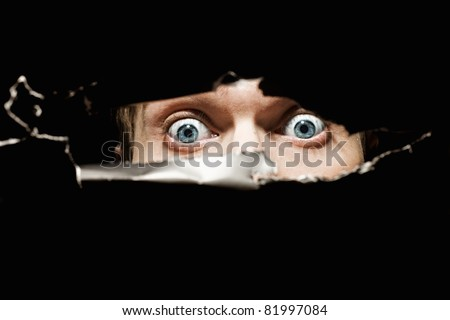 Scary eyes of a man spying through a hole in the wall close up - stock photo