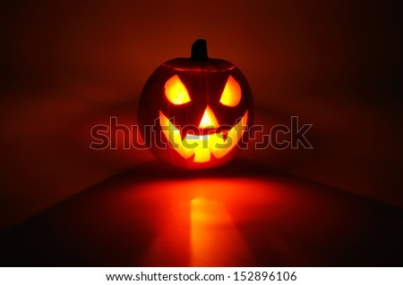 Scary face cut into pumpkin for Halloween (lit from the inside). - stock photo
