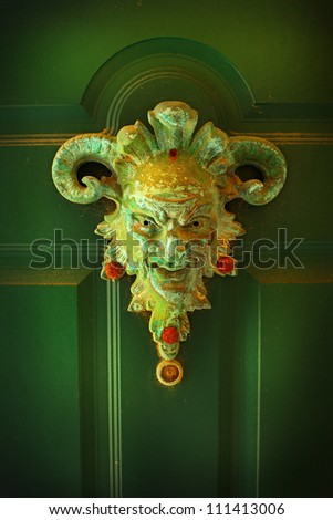 Scary face on a green door - stock photo