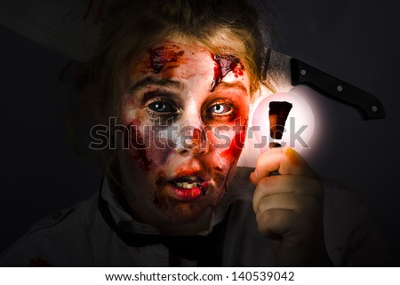 Scary female zombie holding glowing lightbulb with exclamation mark in darkness. Halloween idea - stock photo
