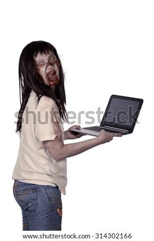 Scary female zombie holding laptop isolated over white background - stock photo