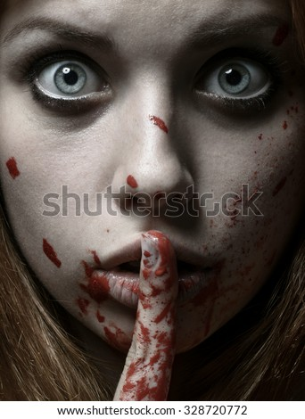 Scary Girl and Halloween theme: portrait of a crazy girl with a bloody face in the studio - stock photo