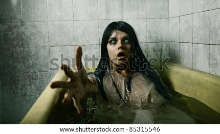 Scary girl in bath stretching her hand to camera, Halloween theme - stock photo