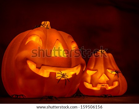 Scary glowing pumpkin with creepy spiders on dark red background, festive border, night of horror, Halloween party - stock photo