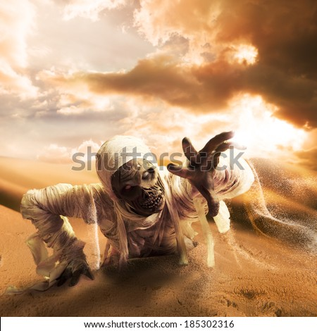 Scary Halloween mummy in hot desert with dramatic lighting and copy space - stock photo