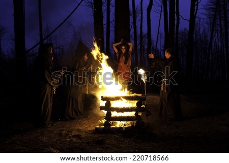 Scary Halloween photo. Men in black clothes, burn the witch at the stake at night in the forest.
