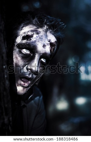 Scary Halloween photo on the head of a horror zombie peeking out from a tree trunk with dumbfounded expression. The human awakening - stock photo