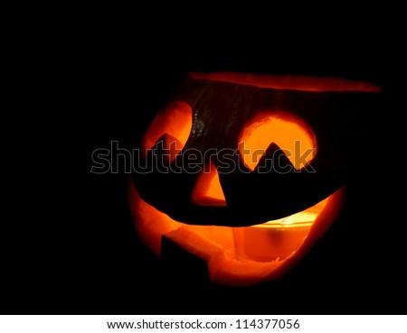 Scary halloween pumpkin jack-o-lantern on black background - stock photo