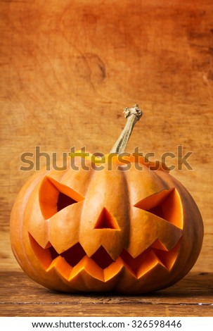 Scary halloween pumpkin on wood background - stock photo