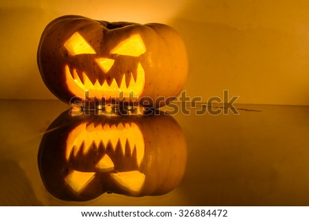 scary Halloween pumpkin with candlelight and reflection. Shallow depth of field - stock photo