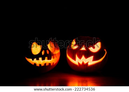 Scary Halloween pumpkins isolated on a black background. Scary glowing faces trick or treat - stock photo