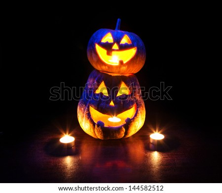 Scary Halloween pumpkins with eyes glowing inside at black background - stock photo