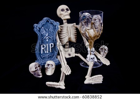 Scary Halloween skeleton with RIP headstone and glass of skeleton skulls.