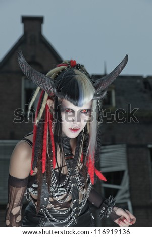 Scary hungry female demon in front of spooky house. - stock photo