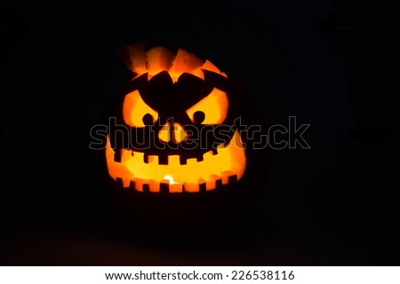 Scary Jack-O-Lantern halloween pumpkin with candle light - stock photo