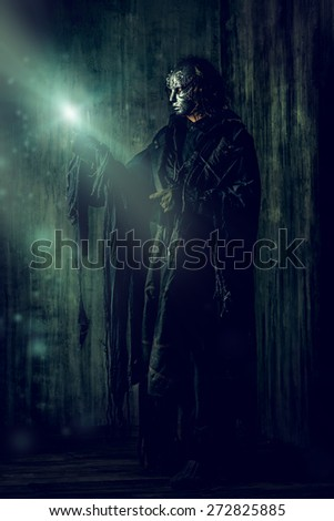 scary man in iron mask and black robe fantasy halloween