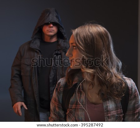 Scary man is about to grab a girl.  Teenage Girl gets attacked by a stranger. - stock photo