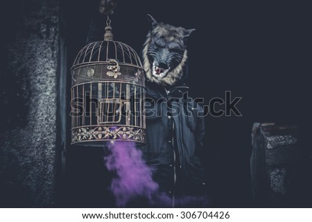 Scary, man with mask wolf and lamp with colored smoke - stock photo
