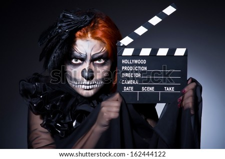 Scary monster with movie board - stock photo