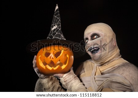 Scary  Mummy holding Halloween pumpkin . Funny smiling young man in mummy costume with holyday pumpkin
