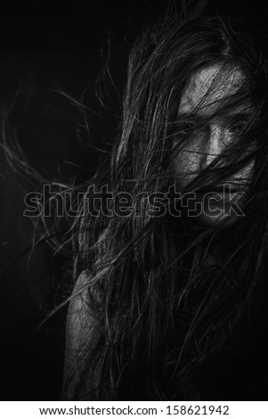 Scary, Portrait of young female beauty with long dark hair in black and white - stock photo