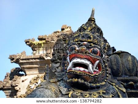 Scary stone barong mask at entrance to Tanah Lot, Bali Indonesia - stock photo