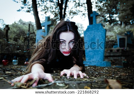 Scary vampire girl with white face and blood coming and looking at camera - stock photo
