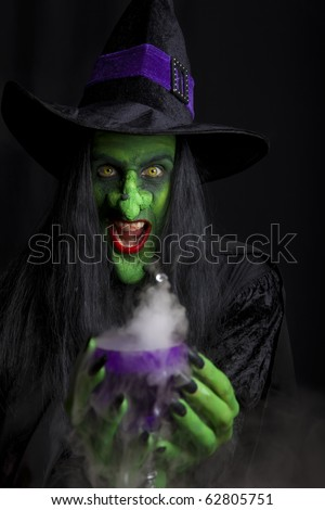 Scary witch holding a smoking Goblet. Low key lighting. - stock photo