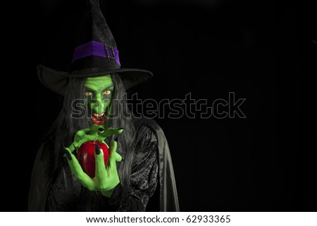Scary witch with a poisonous apple. - stock photo