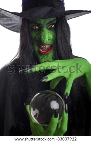 Scary witch with her crystal ball, isolated on white. - stock photo