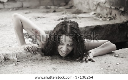 scary woman creeping out of a hole - stock photo