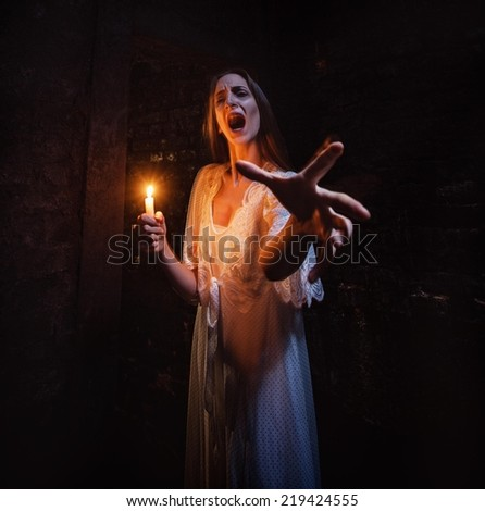 Scary woman standing in a dark hallway with lighten candle and screaming.
